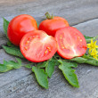 Tomatoes are with leaves and flowers on an old wooden table — Stock Photo