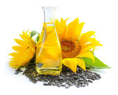 Sunflower oil is with the flowers of sunflower and grain on white background — Stock Photo