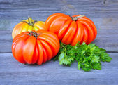 Giant fresh tomatoes (sort Beauty Lottringa) and parsley on an old wooden table — Foto Stock
