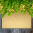 Branches of christmas tree on background the sheet of paper and old wooden table — Stockfoto