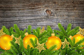 Gold christmas decoration baubles and pine on old wooden background — Stock Photo