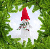 Snowman in frame of branches of fir — Stock Photo
