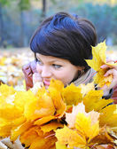 Girl in autumn with maple leaves — Stock Photo