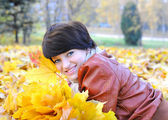 Girl in autumn with maple leaves — Stockfoto