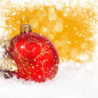 Red christmas ball on gold background with space for text — Stock Photo