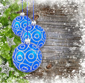 Blue and silver christmas decoration baubles and pine on old wooden background — Stockfoto