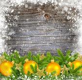 Goldene christbaumkugeln dekoration und kiefer auf einem verschneiten hölzernen hintergrund — Stockfoto