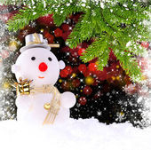 Snow man with by the branches of spruce on a festive background — Stock Photo