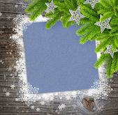 Christmas sheet of paper with the branches of spruce on wooden background with snowflakes — Stock Photo