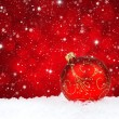 Photo: Red christmas ball on snow on a festive background
