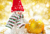 Snowman with Christmas decorations on a festive background — Stock Photo