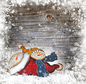 Christmas decoration is a snow man on a wooden snowbound background — Stock Photo