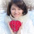 Winter girl with a decorative heart - Stock Photo
