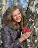 Winter girl with a decorative heart — Stockfoto