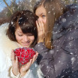 Stock Photo: Two girls with a decorative heart in winter