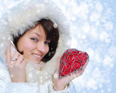 Winter girl with a decorative heart on a festive background — Stock Photo