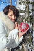 Winter girl with a decorative heart — Stock Photo
