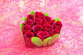 Heart-shaped box with red roses on a background a wrapping paper — Stock Photo