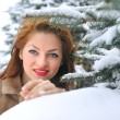 Winter young woman behind snow tree — Stock Photo