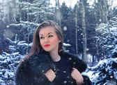 Young woman in winter forest — Stock fotografie