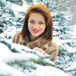 Winter young woman behind snow tree — Stock Photo #19715189