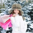 Beautiful happy girl with shopping bags in a winter park - Stock Photo