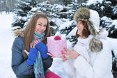 Young beautiful girls in winter with a gift — Stockfoto