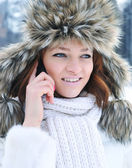 Beautiful young woman with mobile phone in winter — Stock Photo