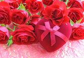 Czerwone róże z pudełko w kształcie serca na tle w opakowaniu — Zdjęcie stockowe