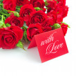 Red roses are with the card of greeting on a white background — Foto Stock