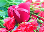 Heart-shaped Gift Box on a background red roses — Stock Photo