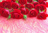 Red roses on a background a wrapping paper — Stock Photo