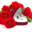 Red velvet box with golden ring and red roses on a white background — Stock Photo