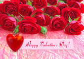 Red roses with a heart on a background a wrapping paper — Стоковое фото