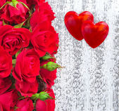 Two hearts with red roses on a wooden background — Stock Photo