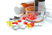 Colorful pills are with glass and bottles on a white background — 图库照片