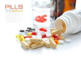 Cápsulas que viertan hacia fuera de una botella sobre un fondo blanco — Foto de Stock
