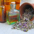 Stock Photo: Dry herbal teChamerion is with tinctures in bottles on sackcloth, herbal medicine