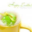 Easter egg in yellow cup on a white background — Stock Photo #22085743