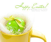 Easter egg in yellow cup on a white background — Stock Photo