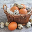 Stock Photo: Different types of eggs in basket on old wooden background