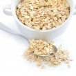 Oat flakes in bowl and spoon on white background — Stock Photo #22893106