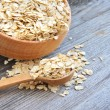 Stock Photo: Oat flakes in bowl and wooden spoon on old wooden background