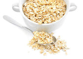 Oat flakes in bowl and spoon on white background — Stock Photo