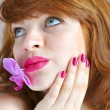 Beautiful girl holding orchid flower in her lips. Focus is on lips — Stock Photo #23605281