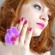 Beautiful girl holding orchid flower in her hands. Focus is on a hand — Stock Photo #25294177