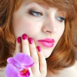 Beautiful girl holding orchid flower in her hands — Stock Photo #25294179