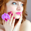 Beautiful girl holding orchid flower in her hands — Stock Photo #25294185
