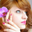 Stock Photo: Beautiful girl holding orchid flower in her hands