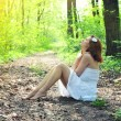 Beautiful young romantic woman in white dress in the spring forest — Stock Photo